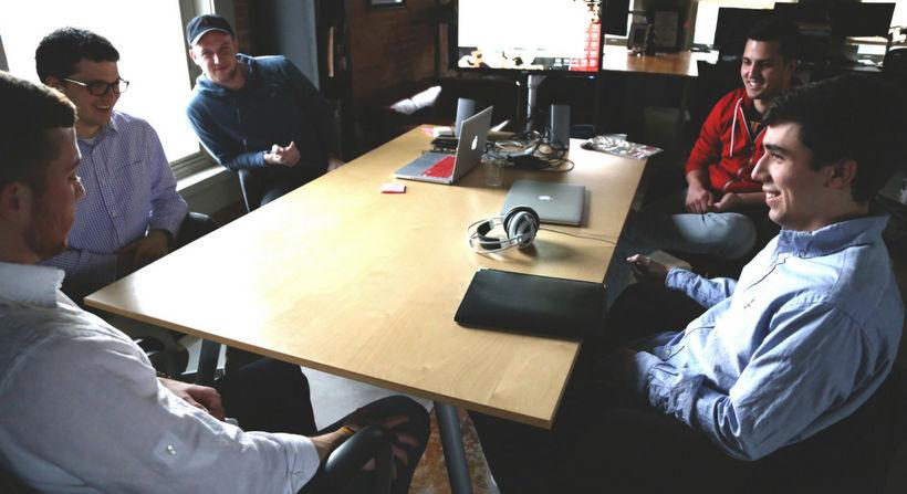 Fünf Männer, am Tisch sitzend
