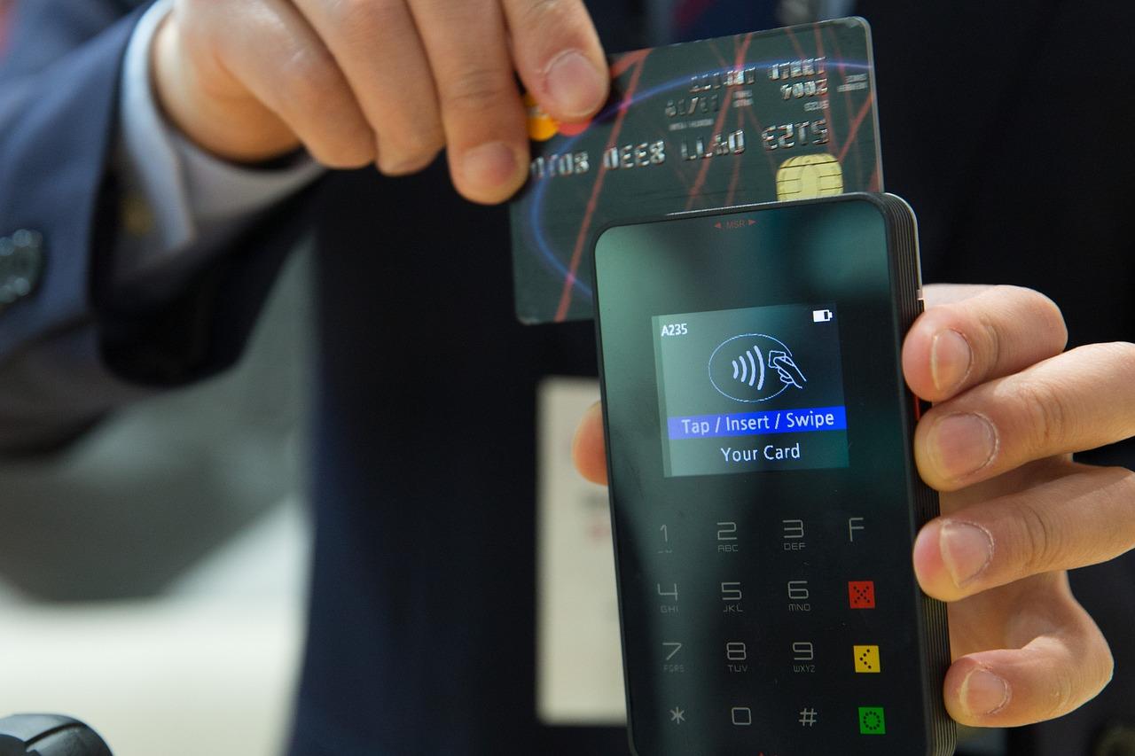 kreditkarte wird an Bezahlgerät gehalten